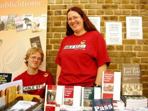 Pippa with her son Blake at the Cable Street bookfair. Pippa standing and her son Blake sitting behind books.