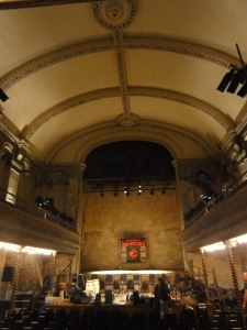 Inside Wilton's Music Hall. Large arching roof. Stage at far end.