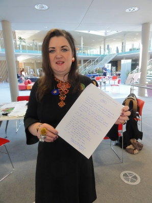 Deborah Tyler-Bennett at the Nottingham Festival of Words, holding the poem written at the Lace Archive, Nottingham Trent University