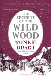 Book cover of The Secrets of the Wild Wood showing a snowy scene with mountains and men fighting on horseback.